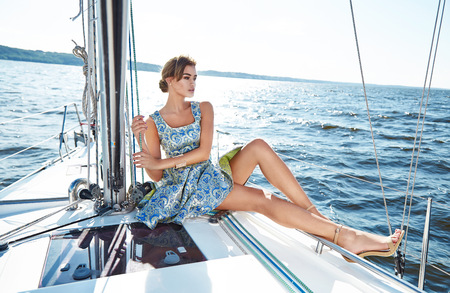 Photo for Beautiful young sexy brunette girl in a dress and makeup, summer trip on a yacht with white sails on the sea or ocean in the Gulf marine of the wind and the breeze in the sun tans romantic - Royalty Free Image