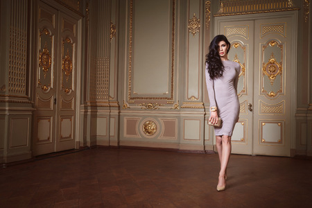 Photo pour Beautiful sexy woman in elegant dress fashionable autumn Collection of spring long brunette hair makeup tanned slim body figure accessories interior luxury castle gold monogram baroque palace of Queen - image libre de droit