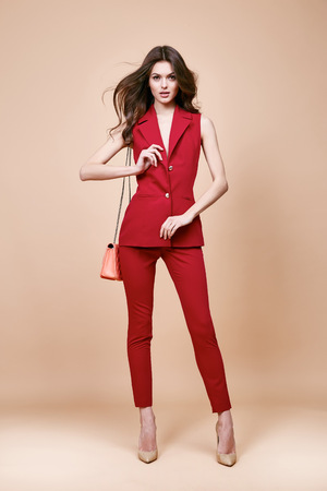 Photo for Beautiful sexy brunette woman wear red silk costume jacket and pants summer collection clothes for business lady casual work office style hold small lather goods bag make a pose fashion model catalog. - Royalty Free Image