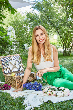 Photo for Beautiful blonde woman happy life style smile, weekend out for a walk in a picnic park in the summer garden, model sits on plaid basket food outdoor recreation warm summer weather flowers bouquet. - Royalty Free Image