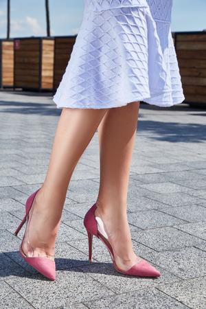 Foto de Beautiful slender legs tanned skin is shod in high-heeled shoes depilation body care catologue stylish fashion collection walks on the street health body care cream white dress denim jacket. - Imagen libre de derechos