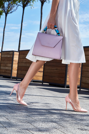 Foto de Beautiful slender legs tanned skin is shod in high-heeled shoes depilation body care catologue stylish fashion collection walks on the street health body care cream white dress bag. - Imagen libre de derechos