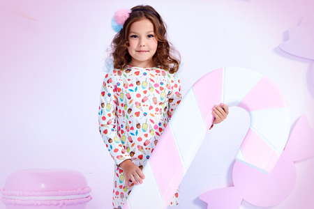 Foto de Small little girl beautiful lady curly hair child wear funny clothes dress socks boots cute face smile sweets baby shower party bar game room birthday hold big candy lollipop macaroons toy play fun. - Imagen libre de derechos