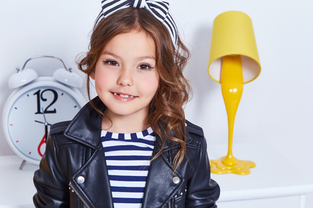 Foto de Portrait of small little lady pretty girl cute kid smile curly brunette hair wear fashion style clothes for baby strip t-shirt lather jacket hat bow play room for game toy fun party furniture color. - Imagen libre de derechos