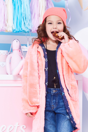 Foto de Portrait of small little girl beautiful lady curly hair child wear funny clothes pink fur hat jeans denim fashion style cute face smile sweets baby shower party candy game room birthday eat chocolate. - Imagen libre de derechos