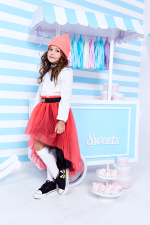 Foto de Small little girl beautiful lady curly hair child wear funny clothes cute face smile sweets baby shower party candy bar game room birthday fashion for lady blouse socks red skirt hat uniform school. - Imagen libre de derechos