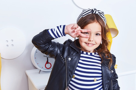Foto de Portrait of small little lady pretty girl cute kid smile hand curly brunette hair wear fashion style clothes for baby strip t-shirt lather jacket hat bow play room for game toy fun party furniture. - Imagen libre de derechos