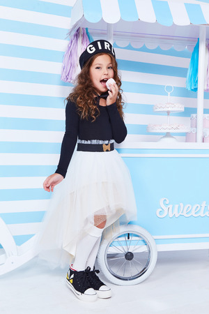 Foto de Beautiful lady curly hair small little girl child funny cute face smile sweets baby shower party candy bar game room birthday wear white skirt black t-shirt beret hat socks clothes blue strip wall. - Imagen libre de derechos