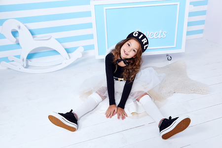 Foto de Small little girl sit on the floor beautiful lady curly hair child wear funny clothes skirt t-shirt hat beret cute face smile sweets baby shower party candy bar game room birthday fun happy play toy. - Imagen libre de derechos