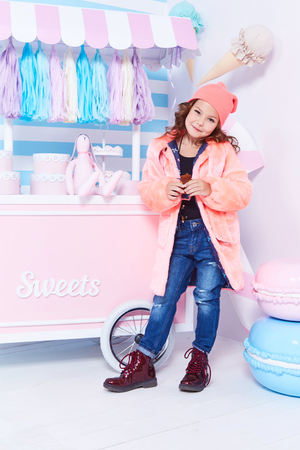 Foto de Clothes for kid jeans denim fur hat fashion style small little girl beautiful lady curly hair child funny cute face smile sweets baby shower party candy bar game room birthday eats chocolate play toy. - Imagen libre de derechos