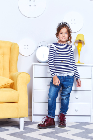 Foto de Fashion style clothes for child small little girl wear strip t-shirt denim jeans boots hat bow cute pretty face curly hair baby model fun play room color furniture yellow chair toy game furniture kid. - Imagen libre de derechos