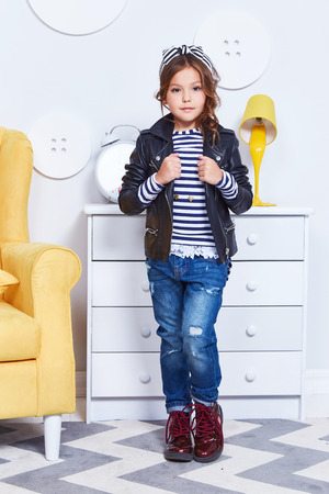 Foto de Fashion style clothes for child small little girl wear strip t-shirt denim jeans lather jacket boots hat bow cute pretty face curly hair baby model fun play room color furniture yellow chair toy game. - Imagen libre de derechos
