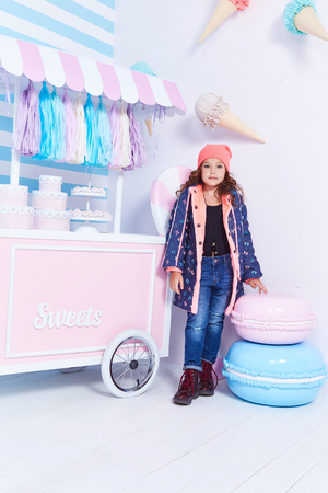 Foto de Small little girl beautiful lady curly hair child cute face smile sweets baby shower party candy bar game room birthday wear funny clothes hat jacket denim jeans toy play fun hold pillow star clothes. - Imagen libre de derechos