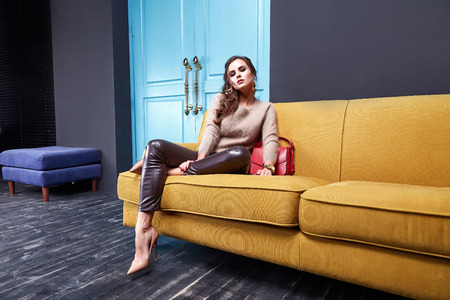 Photo pour Sexy woman beauty makeup wear lather skinny pants cashmere wool sweater fashion clothing style for business lady accessory bag hand watch jewelry interior room furniture sofa blue door glamour model. - image libre de droit