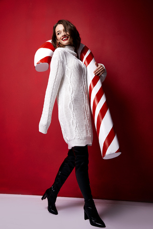 Photo pour Beautiful young pretty woman with a bright evening make-up of shiny red lipstick on the lips brunette hair festive mood knitted sweater winter Merry Christmas New Year and gift surprise candy cane. - image libre de droit