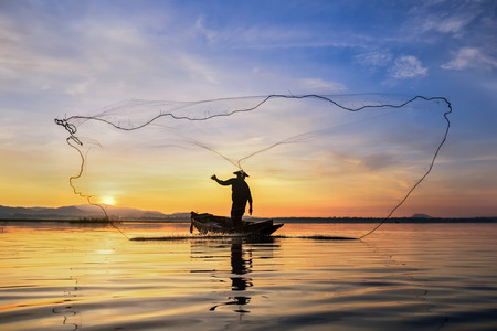 Photo pour Fisherman silhouette on fishing boat with sunset - image libre de droit