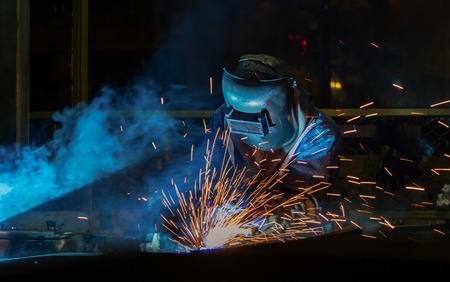 Photo pour Industrial worker is welding metal part in factory - image libre de droit