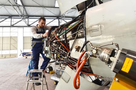 Photo pour Aircraft mechanic repairs an aircraft engine at an airport hangar - image libre de droit