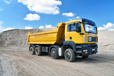 Photo pour Truck transports sand in a gravel pit - gravel mining at an open pit mine - image libre de droit
