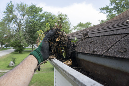 Photo pour Cleaning gutters filled with leaves and sticks. - image libre de droit