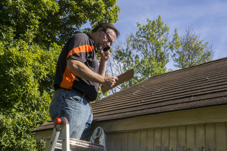 Photo pour Contractor on ladder with cell phone figuring out hail damage repair costs for customer. - image libre de droit