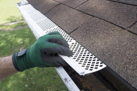 Foto de Contractor adjusting plastic gutter guards to get them to fit. - Imagen libre de derechos