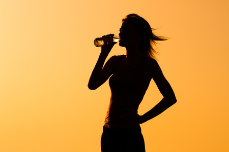 A silhouette of a woman drinking water.