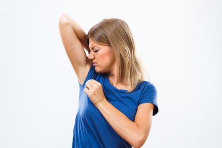 Foto de Young woman is sweating to much and she doesn't like her smell under armpit. - Imagen libre de derechos