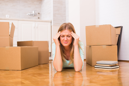 Photo pour Woman is having headache because of moving into new home. - image libre de droit
