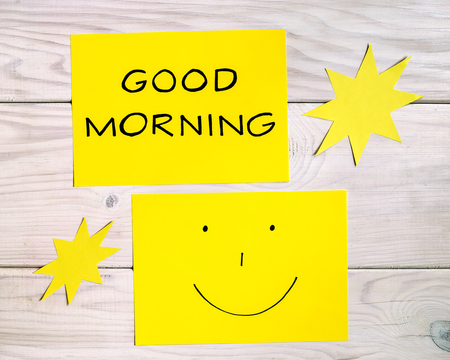 Photo for Text good morning and smiley face with sun shapes on wooden table.Image is intentionally toned. - Royalty Free Image