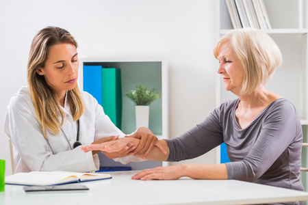 Photo for Female doctor examines her senior patient's wrist in office. - Royalty Free Image
