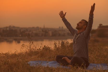 Photo for Man enjoys relaxing in the nature with his arms outstretched after exercising yoga.Image is intentionally toned. - Royalty Free Image
