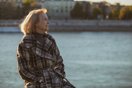 Photo for Senior woman enjoys sitting by the river.Toned image. - Royalty Free Image