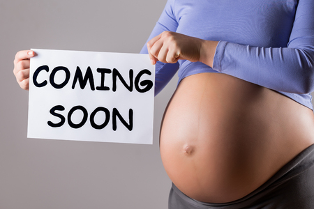Photo pour Image of close up stomach of pregnant woman holding paper with text coming soon on gray background. - image libre de droit