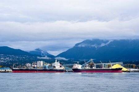 Foto per VANCOUVER, CANADA - OCTOBER 30, 2018:  Two cargo ships are docked in Vancouver Harbour, in front of nearby mountains. - Immagine Royalty Free