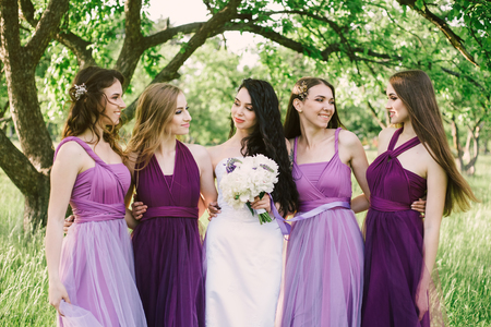 Photo pour Emotional bride and bridesmaids are talking and smiling. Sexy caucasian girls in purple dresses having fun in the park, outdoors. - image libre de droit