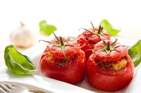 Photo pour Three stuffed tomatoes on a white plate - image libre de droit