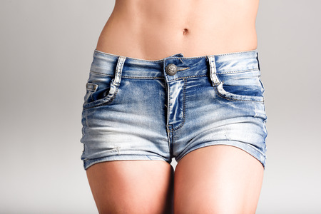Photo for Beautiful woman body in denim jeans shorts on white background - Royalty Free Image