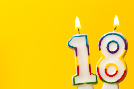 Foto de Number 18 birthday celebration candle against a bright yellow background - Imagen libre de derechos