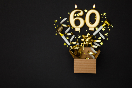 Photo for Number 60 gold celebration candle and gift box background - Royalty Free Image