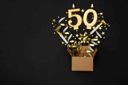 Photo for Number 50 gold celebration candle and gift box background - Royalty Free Image