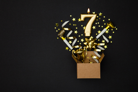 Photo pour Number 7 gold celebration candle and gift box background - image libre de droit