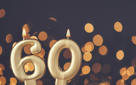 Photo for Gold number 60 celebration candle against blurred light background - Royalty Free Image