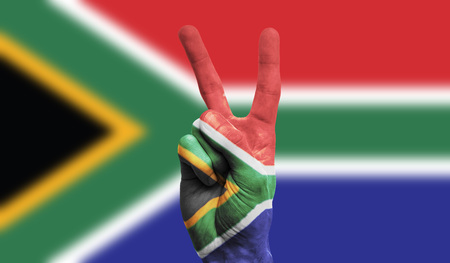 Photo for South Africa national flag painted onto a male hand showing a victory, peace, strength sign - Royalty Free Image