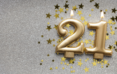 Photo for Number 21 gold celebration candle on star and glitter background - Royalty Free Image