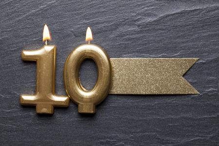 Photo pour Gold number 10 celebration candle with glitter label - image libre de droit