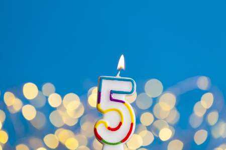 Photo for Number 5 birthday celebration candle against a bright lights and blue background - Royalty Free Image