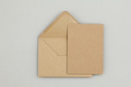 Foto de Blank brown kraft paper card and envelope on a grey background - Imagen libre de derechos