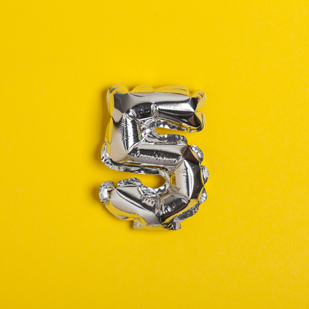 Photo for Silver foil number 5 celebration balloon on a bright yellow background - Royalty Free Image