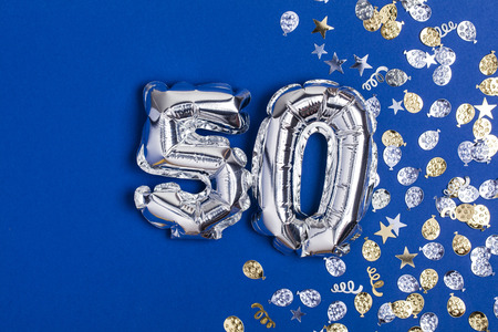 Photo for Silver foil number 50 balloon on a blue background with glitter gonfetti - Royalty Free Image